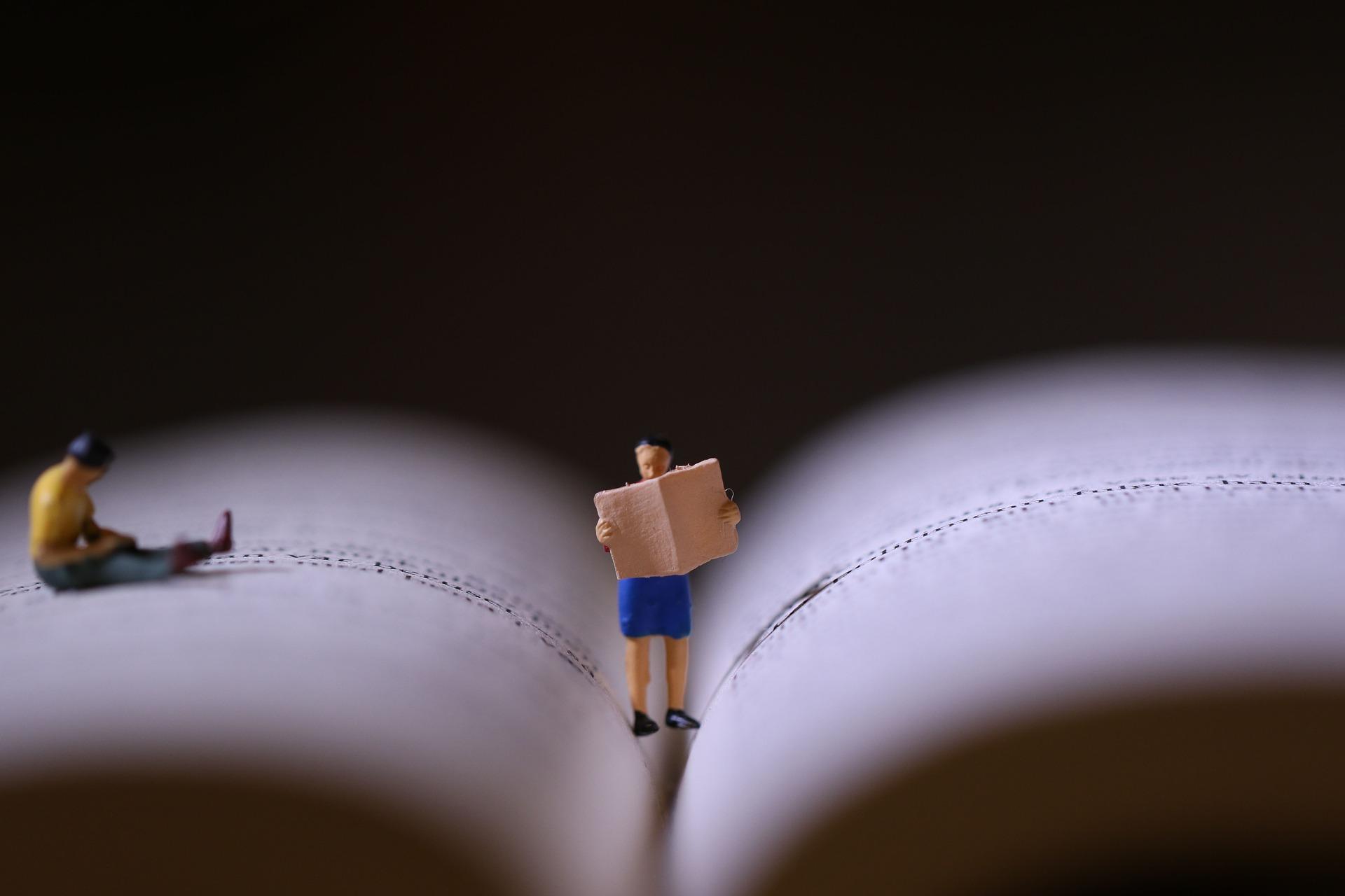 Livre ouvert avec personnages en train de lire